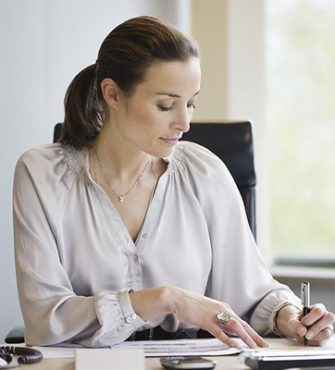 Close up of a woman hand writing a contract with a laptop beside at home or office